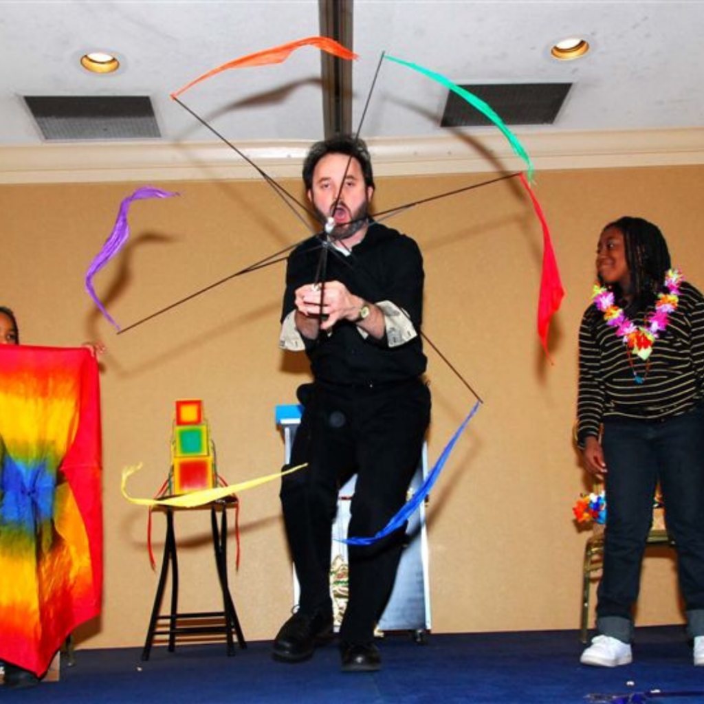 A magician twirls streamers during a trick.