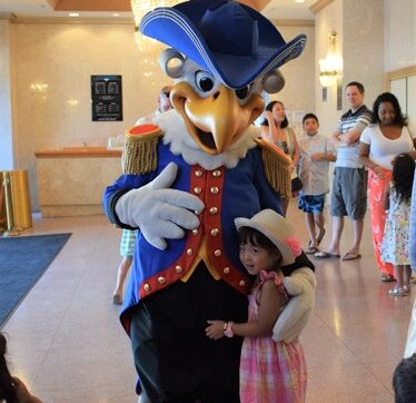 An eagle mascot poses for a photo with a young girl in a hat.
