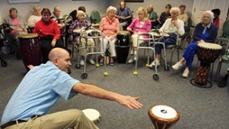 A man reaches for a drum to his right while a audience of nine seniors watch.