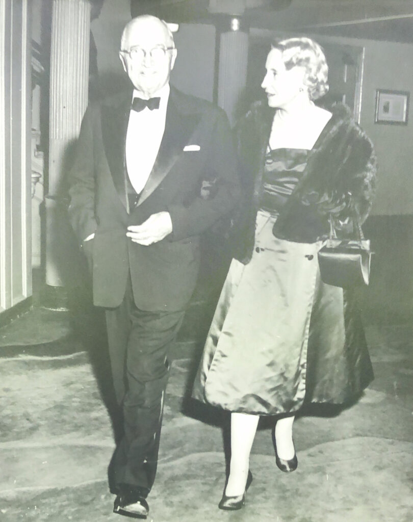 President Truman and Mrs. Truman walk through a lounge at the theatre.