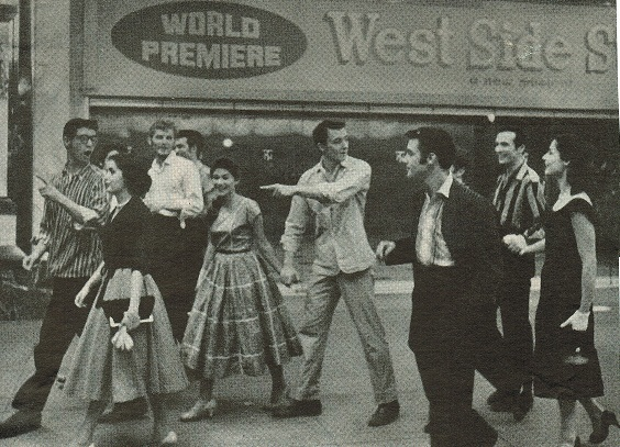 Actors and actresses from West Side Story walk on the sidewalk outside of the theatre.