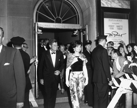 President John F. Kennedy and his wife Jacqueline Kennedy leave The National after a performance with a crowd watching them.