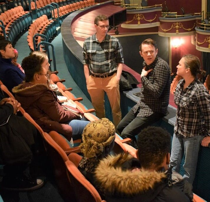 Students sit in auditorium seats listening as cast members share stories from a production.
