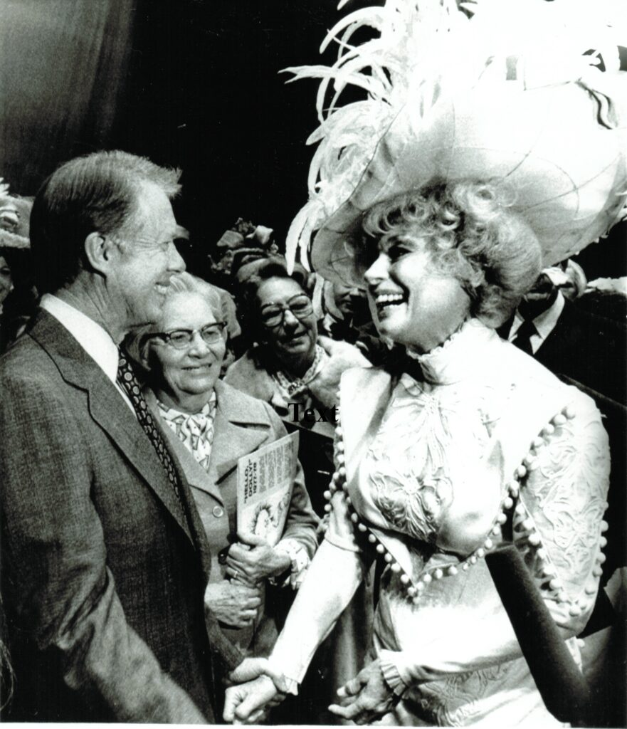 President Jimmy Carter meetings actress with large feathered hat.