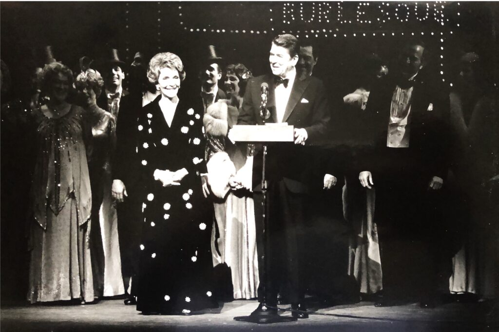 President and First Lady Reagan stand on stage speak from the stage of a performance.